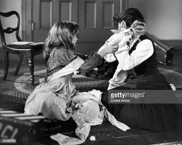 American actors Patty Duke and Anne Bancroft sit on a floor during a lesson in a still from film 'The Miracle Worker' directed by Arthur Penn...