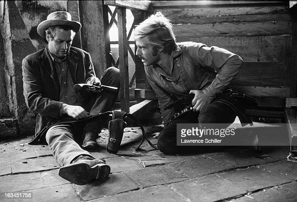 American actors Paul Newman and Robert Redford sit on the floor and check their guns in a scene from the film 'Butch Cassidy and the Sundance Kid'...