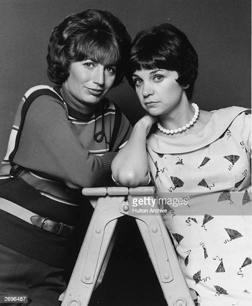 American actors Penny Marshall and Cindy Williams lean towards each other while standing on either side of a ladder in a promotional portrait for the...