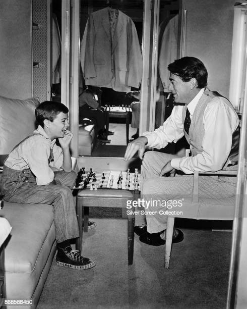 American actors Phillip Alford and Gregory Peck play chess on the set of 'To Kill a Mockingbird' 1962