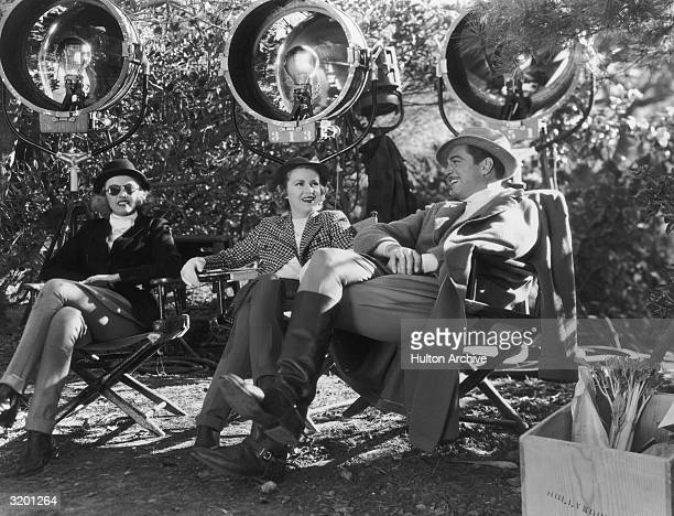 American actors Phillis Brooks Claire Trevor and Michael Whalen sit in director's chairs wearing riding gear chatting during a break from shooting...