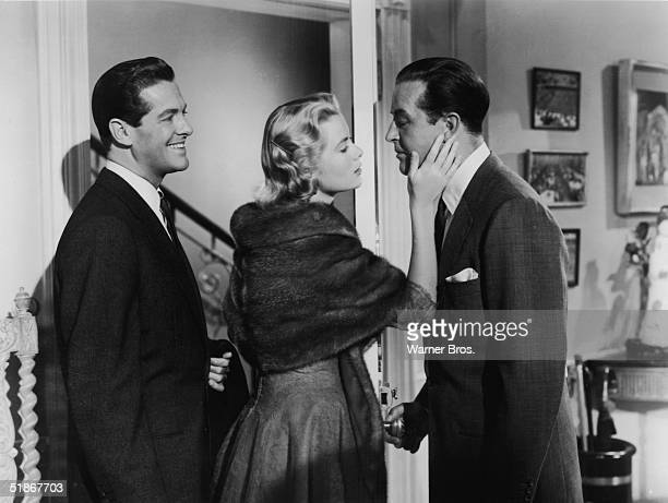"""American actors Robert Cummings and Grace Kelly with Welsh actor Ray Milland in a scene from the film 'Dial """"M"""" for Murder' directed by Alfred..."""