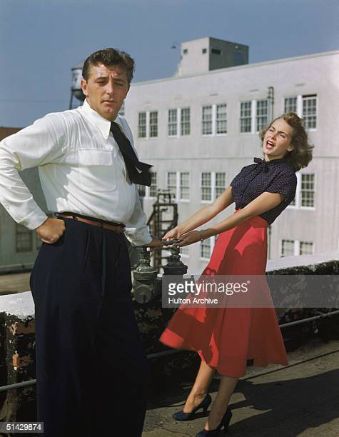 American actors Robert Mitchum and Janet Leigh pretend to have an argument on a roof top late 1940s Leigh leans back as she wears a red skirt and red...