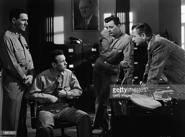 American actors Robert Mitchum and Robert Young talk to two soldiers in a still from the film 'Crossfire,' directed by Edward Dmytryk , 1947.