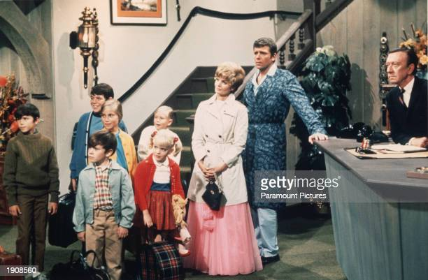 American actors Robert Reed and Florence Henderson stand in a hotel lobby with their television family in a still from the TV series 'The Brady...