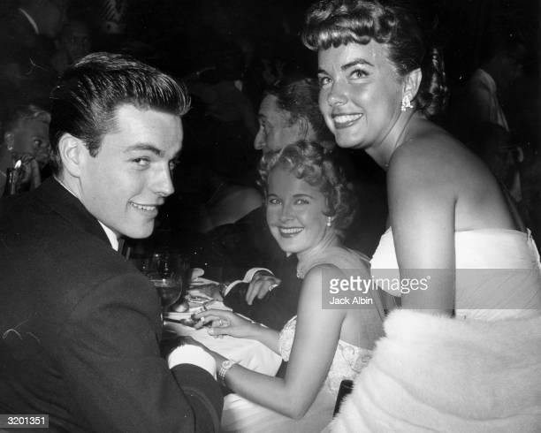 American actors Robert Wagner Mona Freeman and Terry Moore smile as they sit together at Romanoffs' Restaurant following the premiere of director...