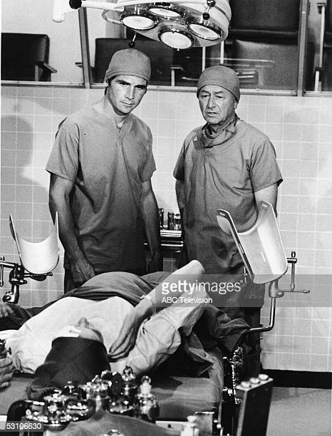 American actors Robert Young and James Brolin both dressed in surgical scrubs and caps stand in an operating room and talk to a patient who lies in a...