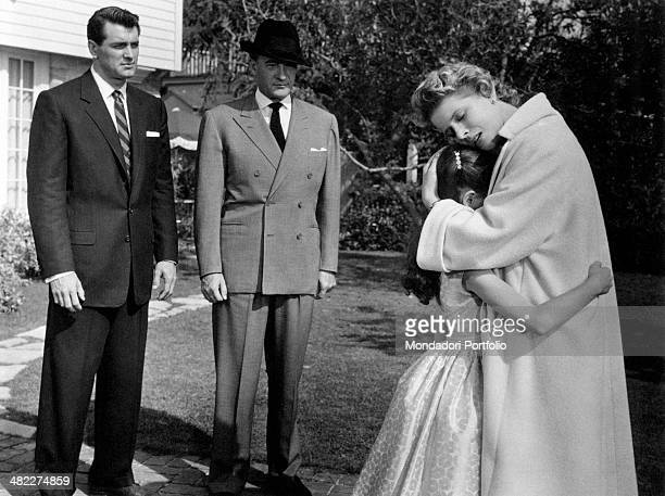 American actors Rock Hudson and George Sanders looking at German actress Cornell Borchers hugging American actress Shelley Fabares in the film Never...