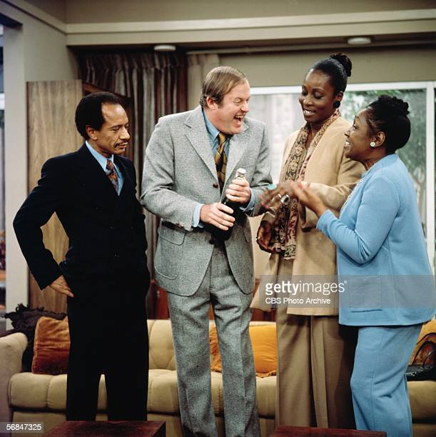 American actors Sherman Hemsley Franklin Cover Roxie Roker and Isabel Sanford interact and laugh together in character respectively as George...