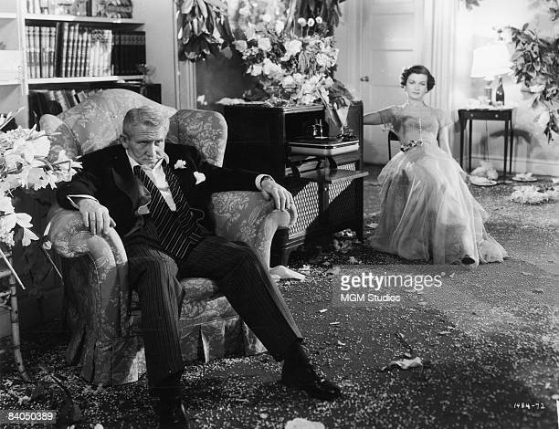 American actors Spencer Tracy and Joan Bennett collapse in separate chairs in a living room littered with confetti in a still from the film 'Father...