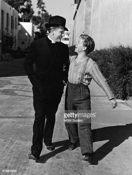 American actors Spencer Tracy and Mickey Rooney walk arm in arm along a street at the MGM Studio during the filming of 'Boys' Town' directed by...