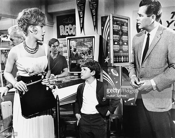 American actors Stella Stevens and Ronny Howard and Canadianborn actor Glenn Ford strike up a friendship in a penny arcade in this still from the...