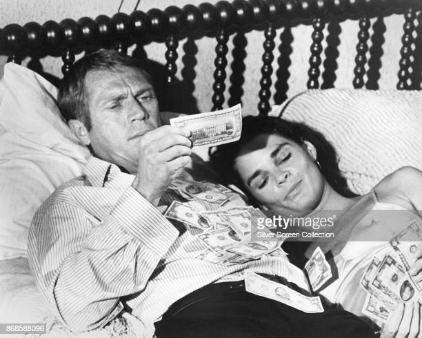 American actors Steve McQueen and Ali MacGraw lie in bed covered by money in a scene from the film 'The Getaway' 1972
