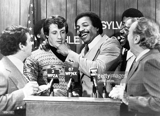 American actors Sylvester Stallone and Carl Weathers clown together during a press conference in a still from the film, 'Rocky,' directed by John G....