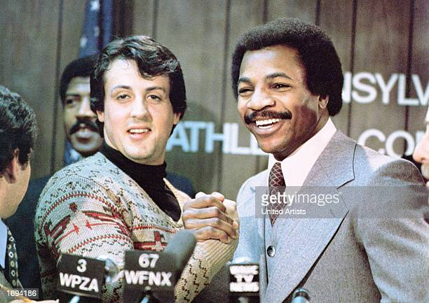 American actors Sylvester Stallone and Carl Weathers grip hands and smile together during a press conference in a still from the film 'Rocky'...