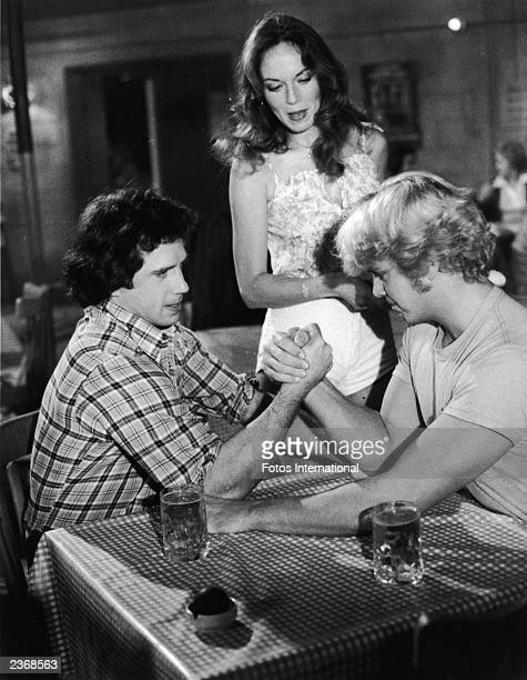 American actors Tom Wopat and John Schneider arm wrestle as Catherine Bach watches in a still from the television series, 'Dukes of Hazard,' circa...