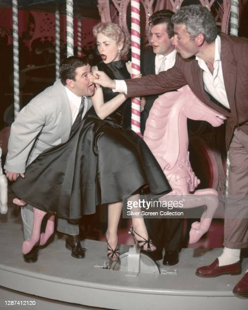 American actors, Tony Curtis and Jeff Chandler visiting Buddy Hackett and Janet Leigh , on the set of the musical, 'Walking My Baby Back Home', 1953.