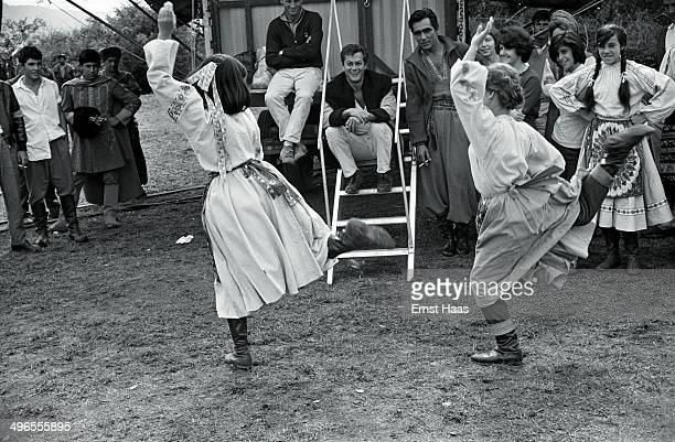 American actors Tony Curtis and Perry Lopez and other crew members watching a pair of young Cossack dancers on the set of the film 'Taras Bulba' 1961