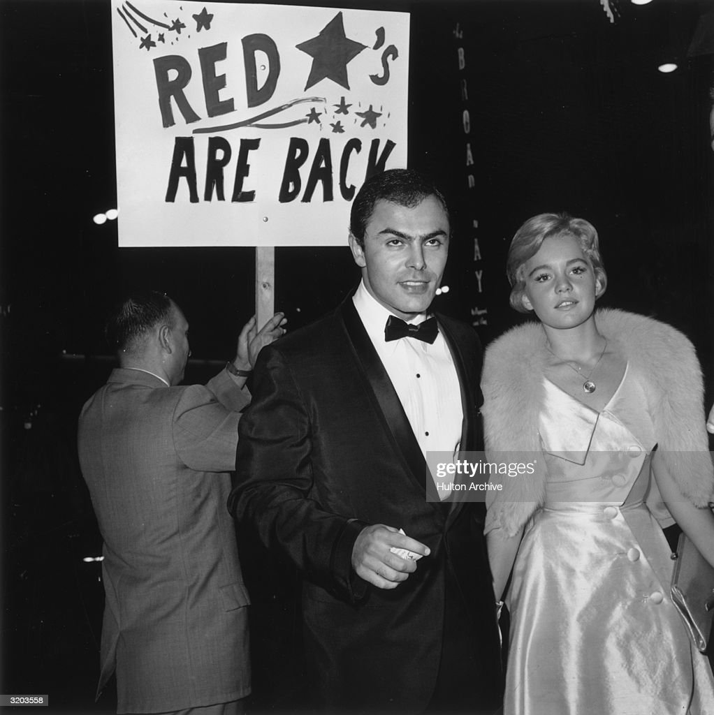 American actors Tuesday Weld and John Saxon walk in front of a man carrying a 'RED STARS ARE BACK' placard at the premiere of director Stanley Kubrick's film 'Spartacus.' Weld wears a satin dress and fur stole. Saxon wears a tuxedo.