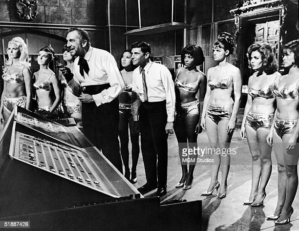 American actors Vincent Price and Dwayne Hickman are surrounded in a lab by unidentified actresses in bikinis in a still from the film 'Dr Goldfoot...