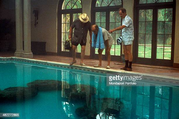 American actors Wilford Brimley Hume Cronyn and Don Ameche observing the cocoons laid down by the aliens in a swimming pool in the film Cocoon 1985