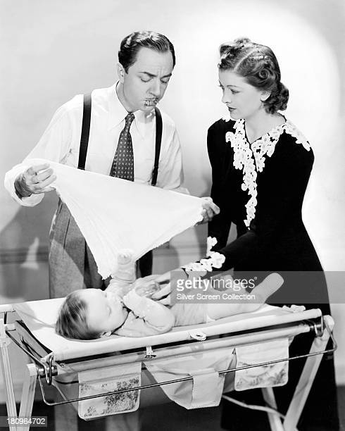 American actors William Powell and Myrna Loy as Nick and Nora Charles changing their baby's nappy in a publicity still for 'Another Thin Man'...