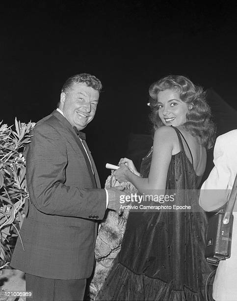 American actress Abbe Lane, wearing a tulle dress and holding a fur, portrayed while signing an autographs with her husband and manager Xavier Cugat,...