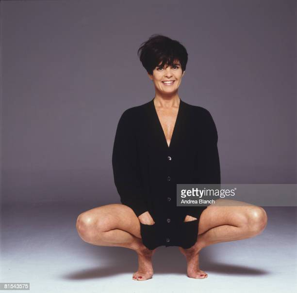 American actress Ali MacGraw smiles smiles and squats on her toes during a photoshoot for Mirabella magazine, 1999.