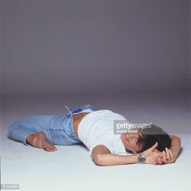 American actress Ali MacGraw smiles while she lies on the floor, her legs folded beneath her and her jean unzipped, during a photoshoot for Mirabella...