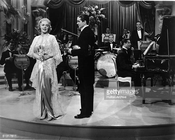 American actress Alice Faye sings as American actor Tyrone Power holds his violin in a film still from 'Alexander's Ragtime Band' a musical featuring...