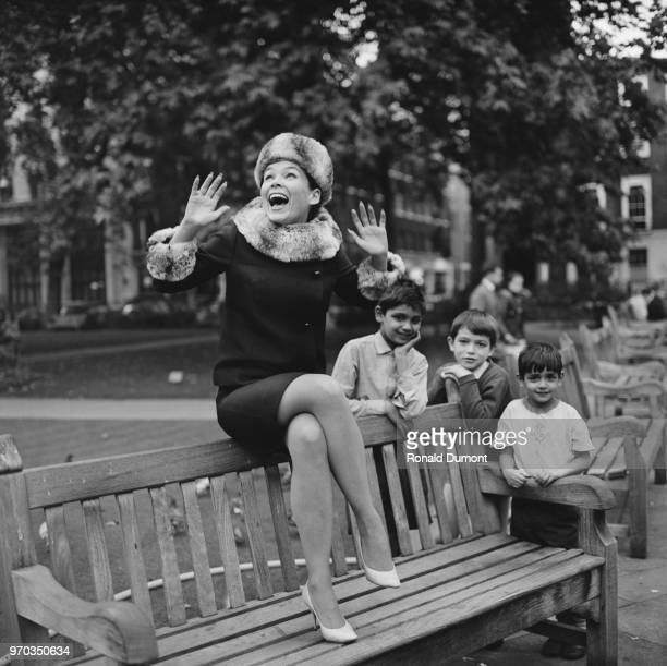 American actress and ballet dancer Yvonne Craig sitting on a bench while three children stand in the background UK 20th September 1967 She is mostly...