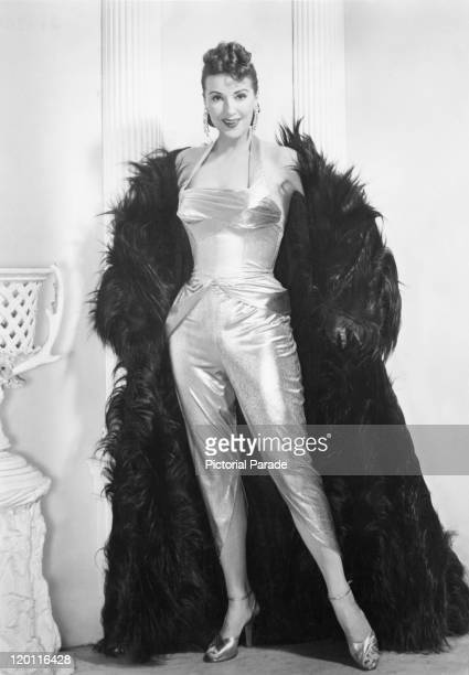American actress and burlesque entertainer Gypsy Rose Lee wearing an outfit with silver trousers and a feather cape circa 1950