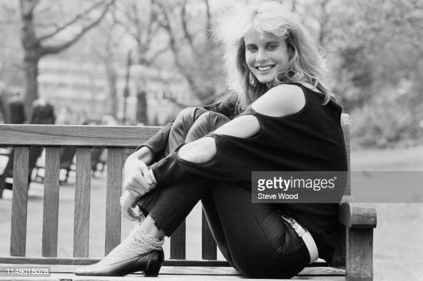 American actress and cellist Lori Singer sitting on a bench in a park UK 10th April 1984