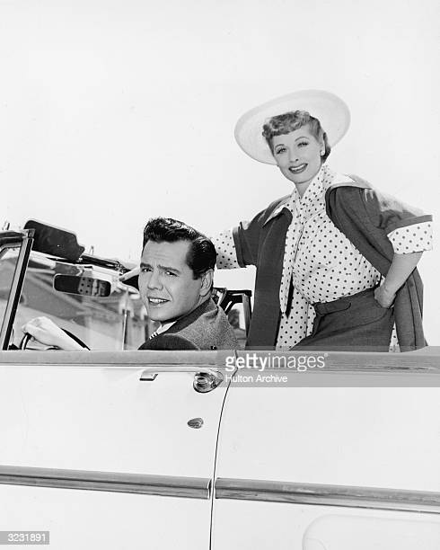 American actress and comedian Lucille Ball and her husband, Cuban-born actor and bandleader Desi Arnaz , pose in a convertible in a promotional...