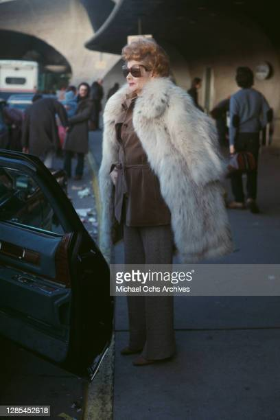 American actress and comedian Lucille Ball , wearing a white fur coat over a brown blouse and grey trousers, as she stands wearing sunglasses...