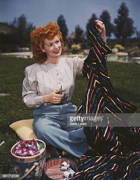 American actress and comedienne Lucille Ball sits outdoors and prepares to cut a piece of striped fabric with apaior of scissors 1940s