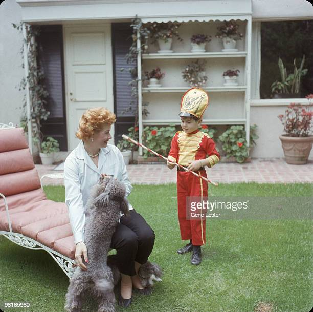 American actress and comedienne Lucille Ball watches as her son Desi Arnaz Jr dressed as a drum major twirls a baton in the back yard of their home...
