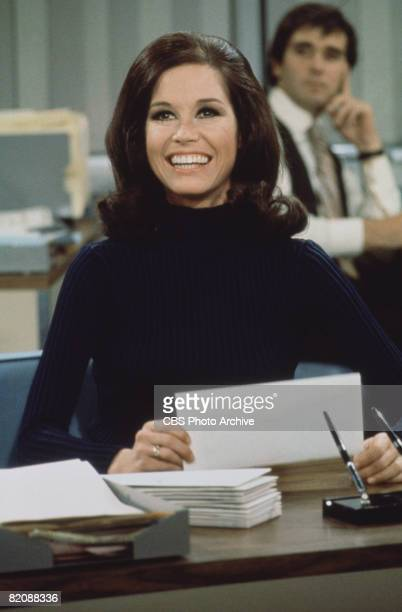 American actress and commediene Mary Tyler Moore smiles broadly as she sits at a desk in a scene from 'The Mary Tyler Moore Show' , Los Angeles,...