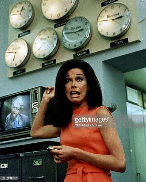 American actress and commediene Mary Tyler Moore, wearing a belted and sleeveless orange dress, worriedly points to an array of wall-mounted clocks...