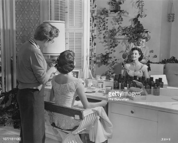 American actress and dancer Cyd Charisse has her hair arranged by MGM stylist Mary Keats in her private dressing room circa 1955 Charisse designed...