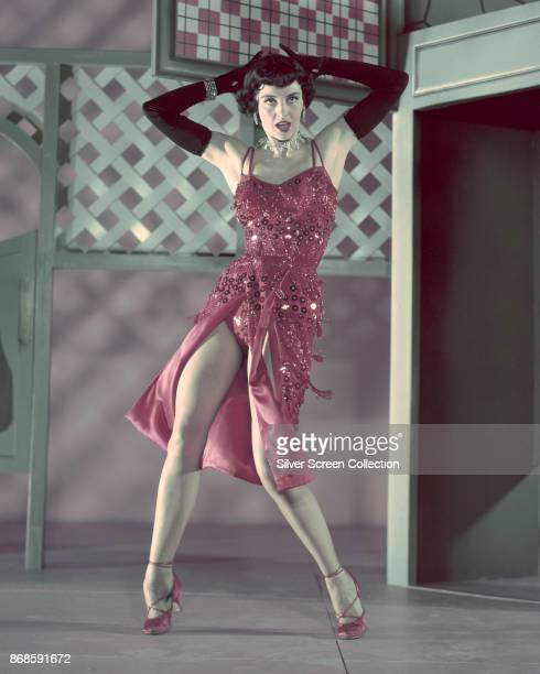 American actress and dancer Cyd Charisse in black elbow gloves and a red sequin dress dances in a scene from the film 'The Band Wagon' Culver City...