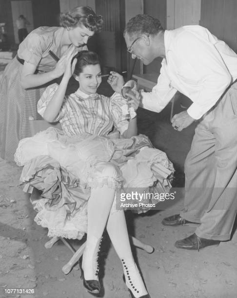 American actress and dancer Cyd Charisse is checked over by hairdresser Peggy Shannon and makeup artist Lee Stanfield before her dance number 'The...