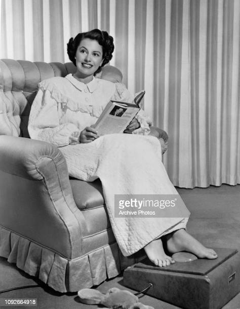 American actress and dancer Cyd Charisse reading a book by Harold Robbins in her nightgown circa 1954