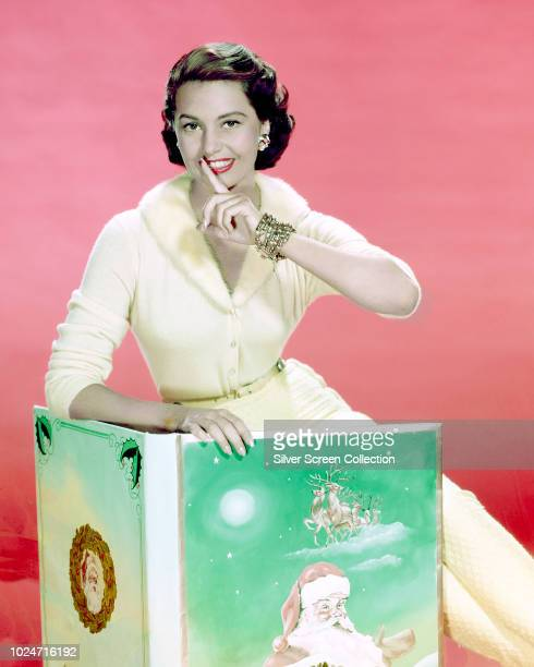 American actress and dancer Cyd Charisse reads a Christmas book circa 1950