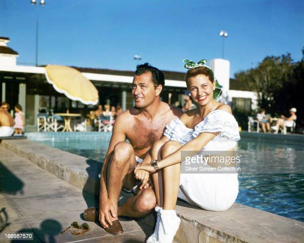 American actress and dancer Cyd Charisse sitting by a swimming pool with her husband dancer Nico Charisse circa 1945