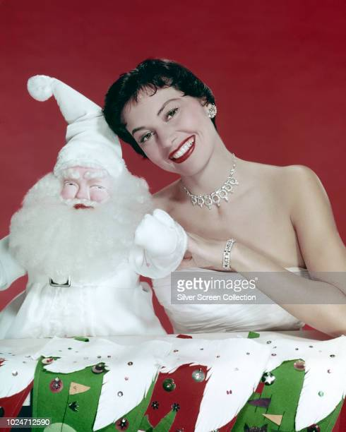 American actress and dancer Cyd Charisse with a model of Santa Claus circa 1950