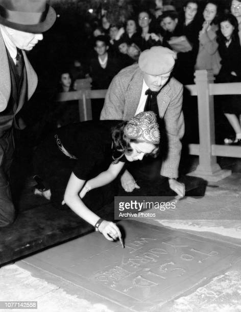 American actress and dancer Eleanor Powell writes an inscription to Sid Grauman in wet cement outside Grauman's Chinese Theatre in Hollywood...
