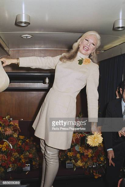 American actress and dancer Ginger Rogers in a railway carriage compartment as she arrives in London by train prior to beginning her starring role in...