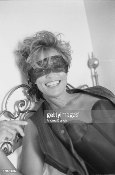 American actress and model Lauren Hutton dressed in an unbuttoned sleevless shirt and a bustier leans back on a bed and laughs her eyes wrapped in...