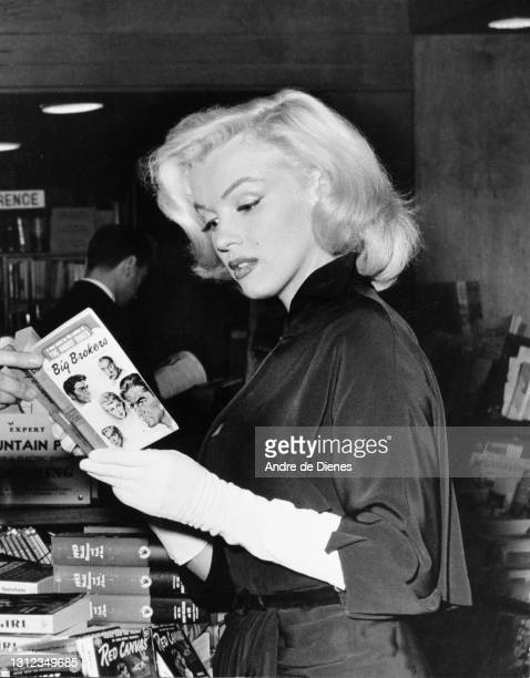 American actress and model Marilyn Monroe reads a copy of Irving Shulman's novel 'The Big Brokers' at a bookstore , Beverly Hills, California, 1953.